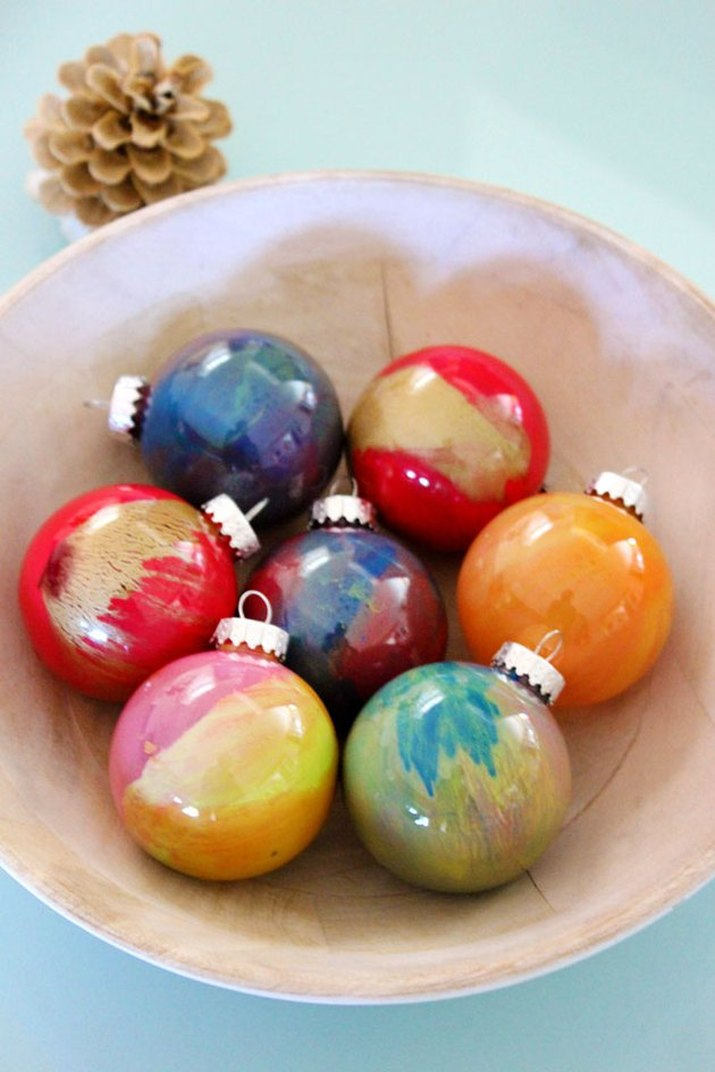 Colorful hand-painted glass ball decorations in a shallow bowl, shot from above, on a pale blue countertop with a pine cone to the rear