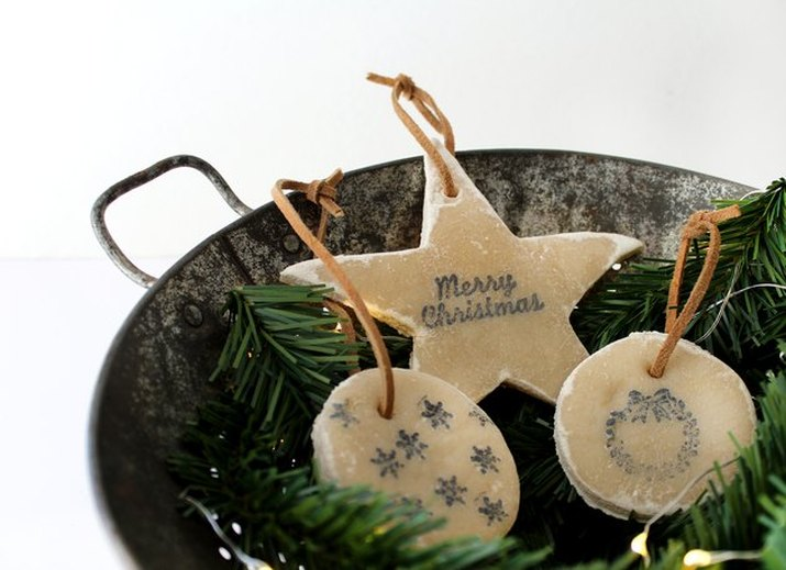 Three handmade salt dough decorations, each stamped with Christmas-themed images, displayed on evergreen boughs in a rustic galvanized bucket