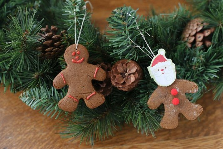 Gingerbread-man cookie ornaments hanging from an evergreen wreath