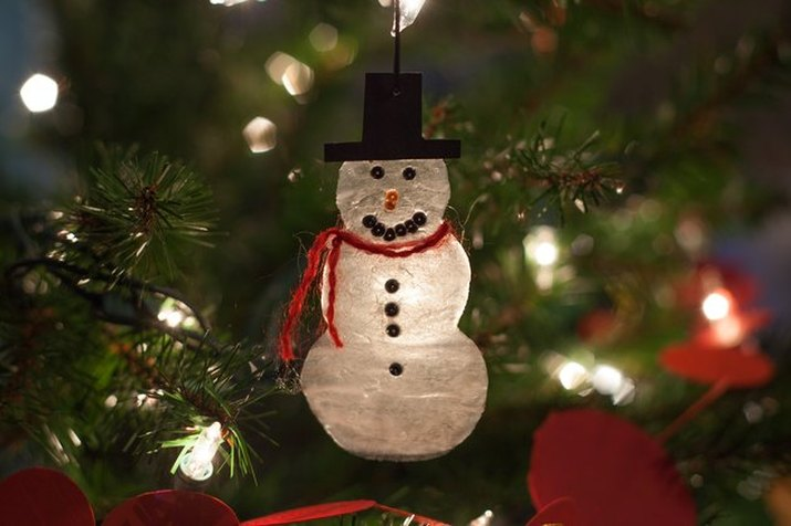 DIY decoration of a snowman with top hat and red scarf, hanging from a Christmas tree and illuminated from behind by one of its lights
