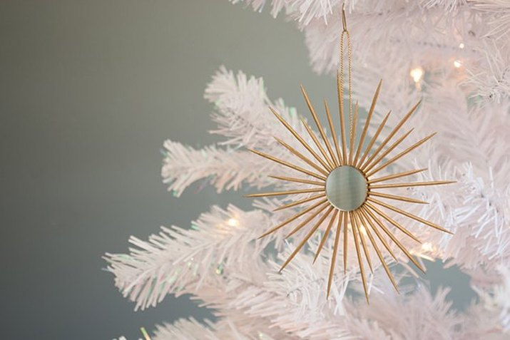 DIY ornament consisting of a small circular mirror surrounded in a sunburst pattern by gold-painted toothpicks, hanging from a white Christmas tree
