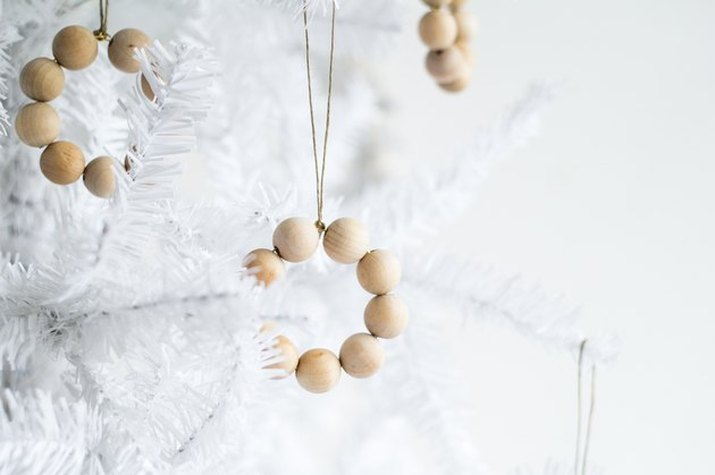 Rings of pale wooden beads, suspended by gold-colored cord from a white Christmas tree, on a white background