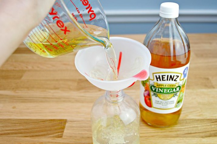 An image of apple cider vinegar being poured into a jug.