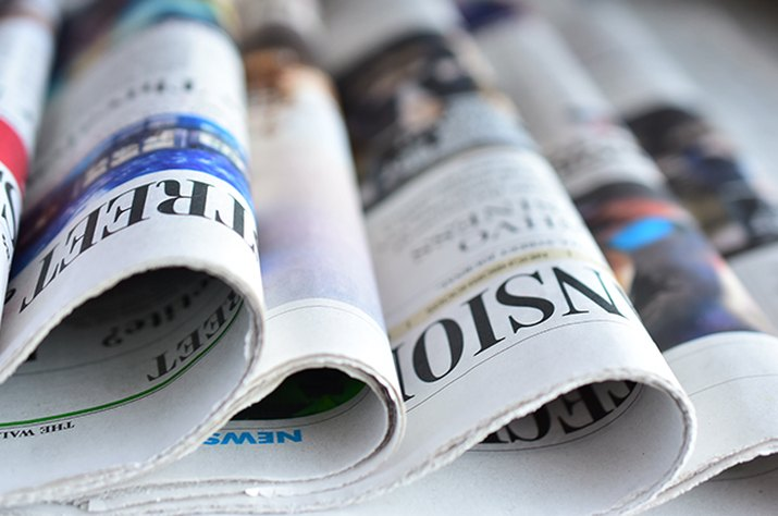 An image of newspapers laid out on a table.
