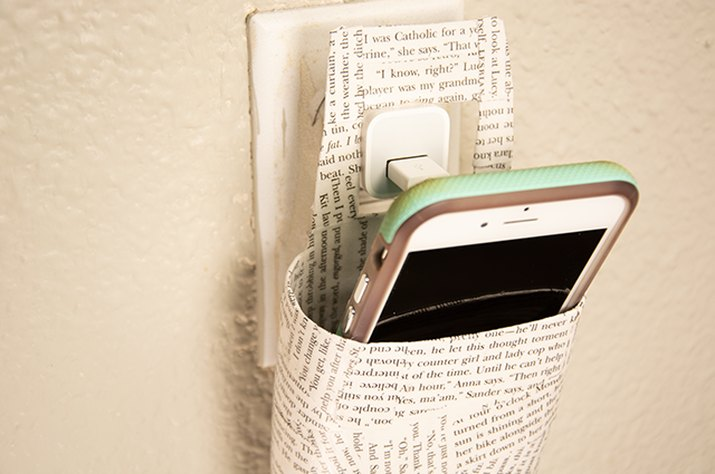 An image of a decoupage phone-charging holder made from an old lotion bottle.