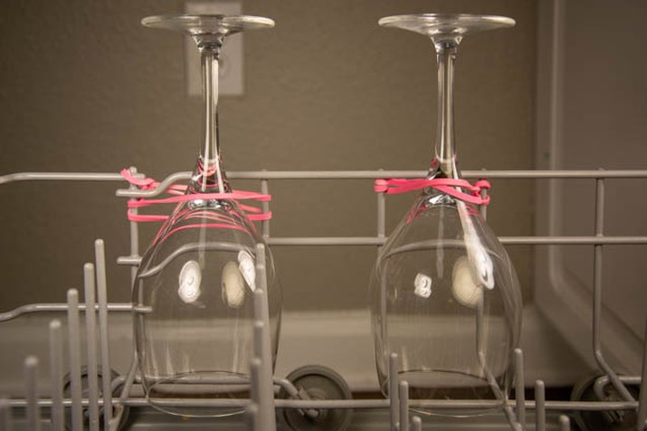 An image of wine glasses in a dishwasher rubber band hack