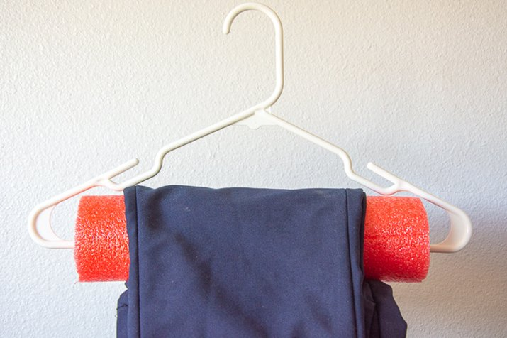 use a pool noodle on a hanger to keep pants straight