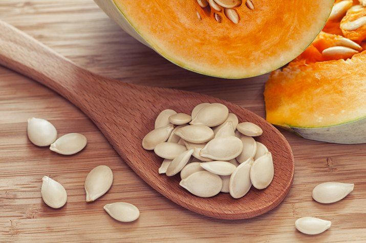 Pumkin seeds inside of wooden spoon