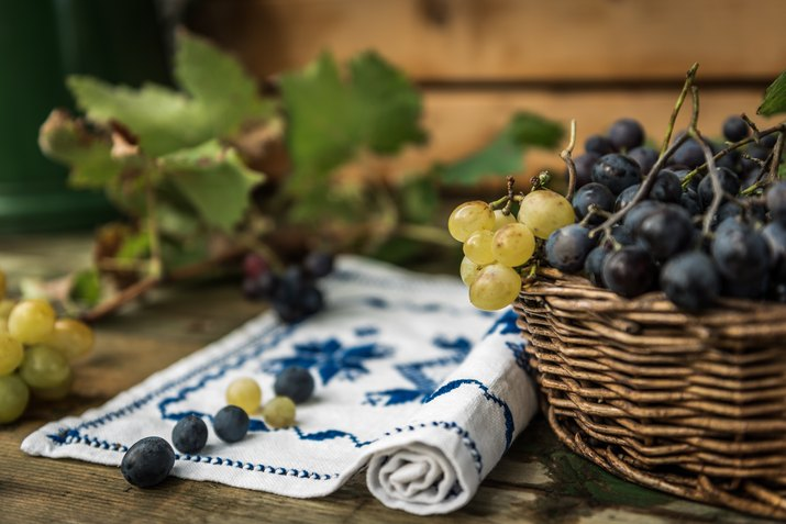 Close-Up Of Grapes In Wicker Basket On Table