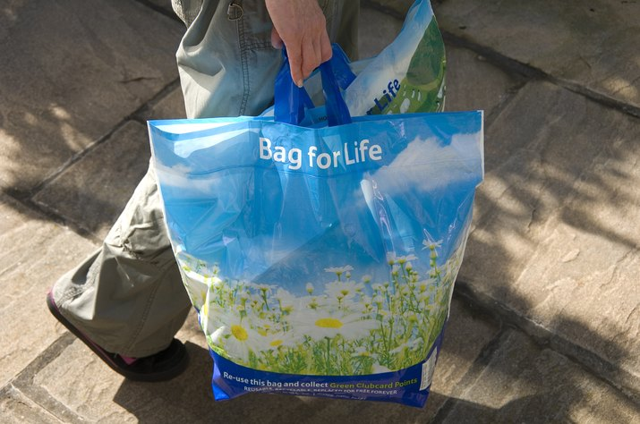 Woman carrying reusable plastic shopping bags