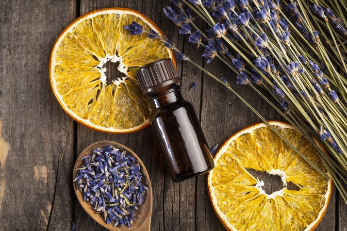 Essential oil lavender and orange dry on a wooden table, top view