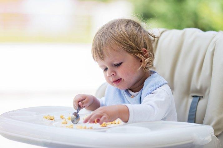Cute baby eating breakfast in high chair.