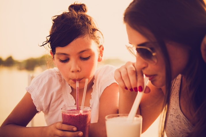 Mother and daughter drinking juice at cafe