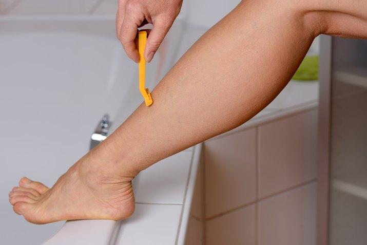 Low Section Of Woman Using Yellow Razor On Leg In Bathroom