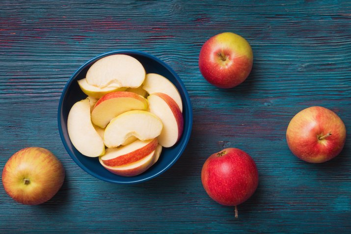 Red apples with slices over blue wooden background