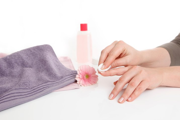 Cropped Hands Of Woman Removing Nail Polish Against White Background