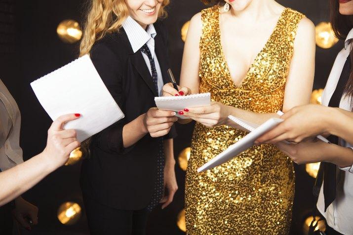 Superstar woman wearing golden shining dress crowded by paparazzi