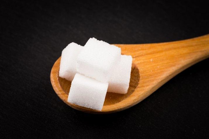 White refined sugar in wooden spoon on dark stone background