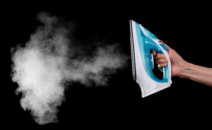 Steam iron in female hand isolated on black background.