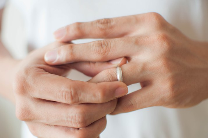 A young man is removing his wedding ring a concept of relationship difficulties