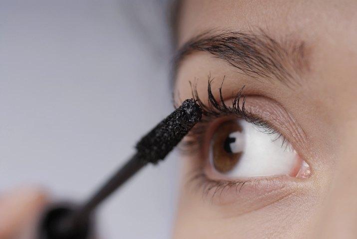 Close-up of a young woman applying mascara