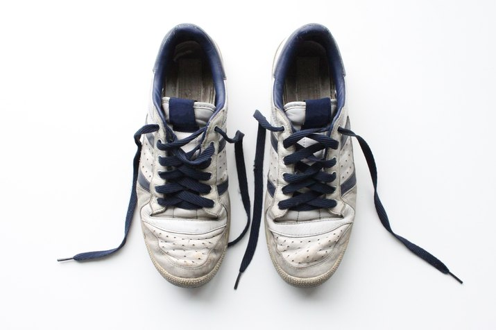 Pair of worn, white vintage sneakers shot from above