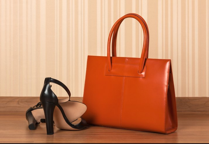 Women black leather shoes with clutch bag, on wood floor