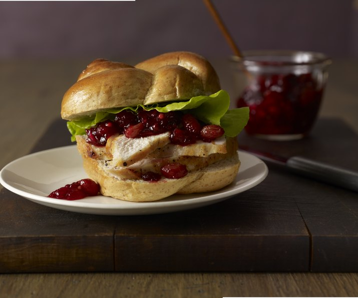 A chicken sandwich with cranberry chutney and lettuce witting on a plate next to a glass jar of chutney.