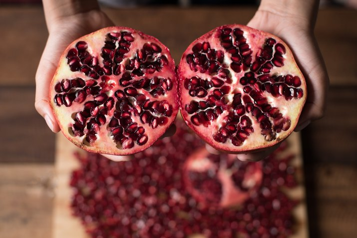 Cropped Hands Of Person Holding Pomegranates