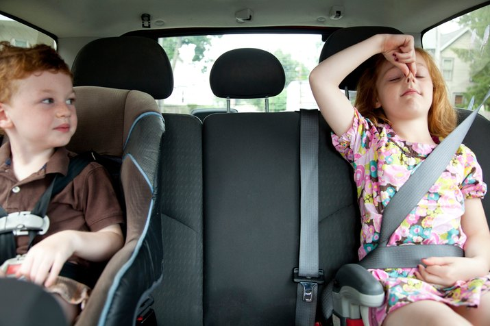 Girl making faces in car with little brother