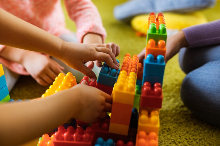 Close up of unrecognizable kids playing with toy blocks on carpet.
