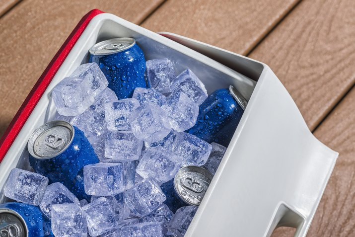 Cooler full of ice cold drinks cans