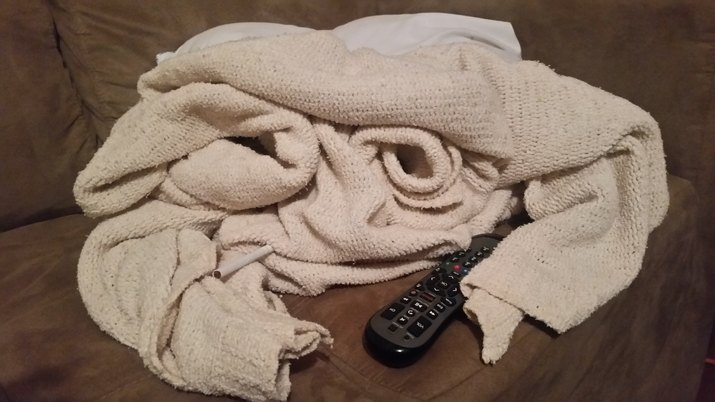 Close-Up Of Knitted Blanket With Remote On Sofa