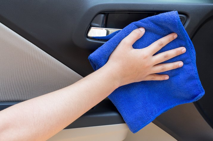 Cropped Hand Of Woman Wiping Car With Blue Towel