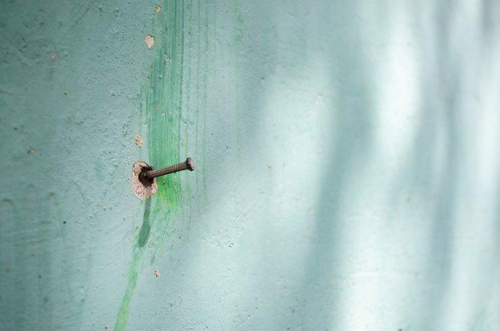 Nail on a green wall.