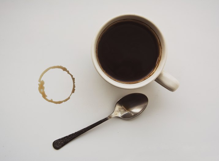 Stain from a cup of coffee, black coffee and a little spoon, white background