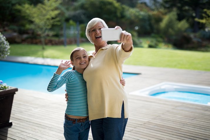 Granddaughter and grandmother taking a selfie near the pool