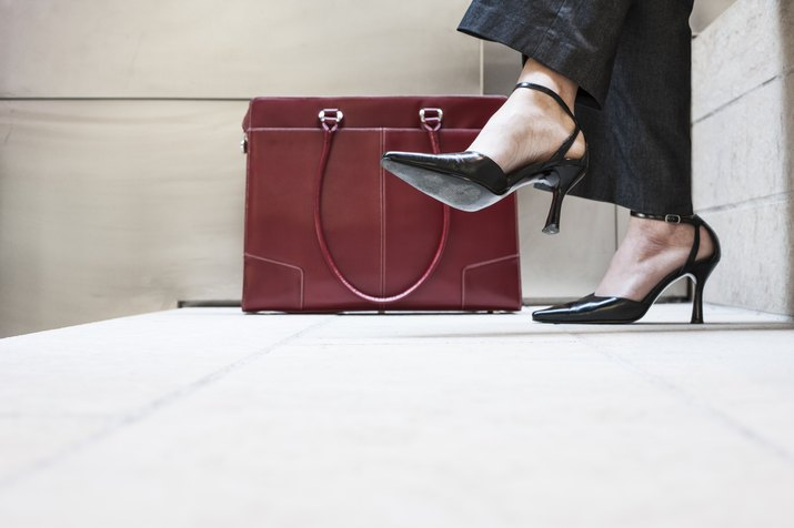 Businesswomans feet in high heeled shoes and her purse.