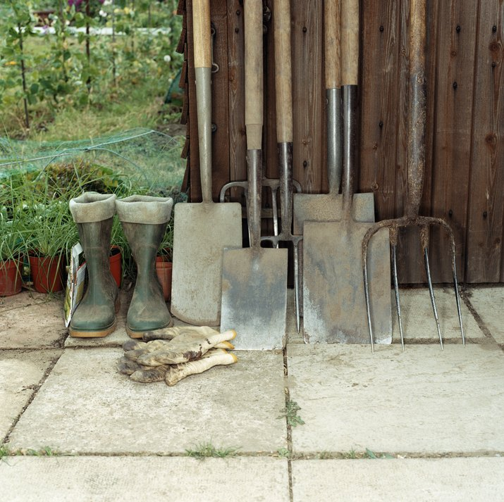 Spades, rake, boots and gardening gloves by a shed