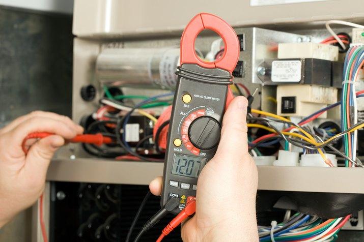Repairman Checks Voltage on Geothermal HVAC System