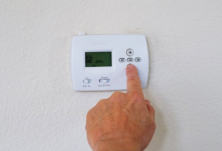 Cropped Hand Of Man Adjusting Thermostat On Wall