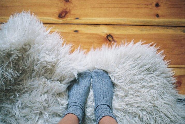 Womans feet wearing socks on a rug
