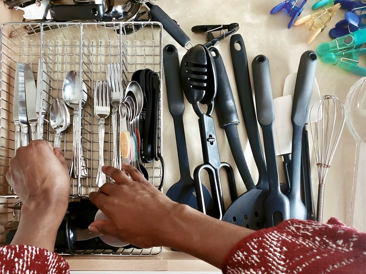 Close-Up of Woman Arranging Spoons in Cutlery Drawer