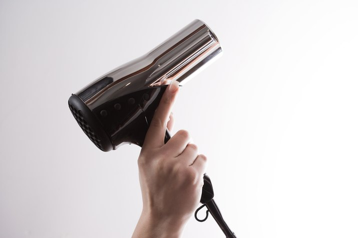 Woman holding hairdryer