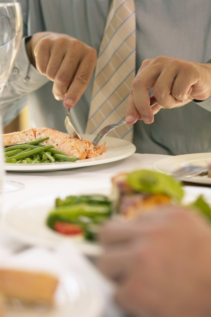 Businessman eating at restaurant table, mid section
