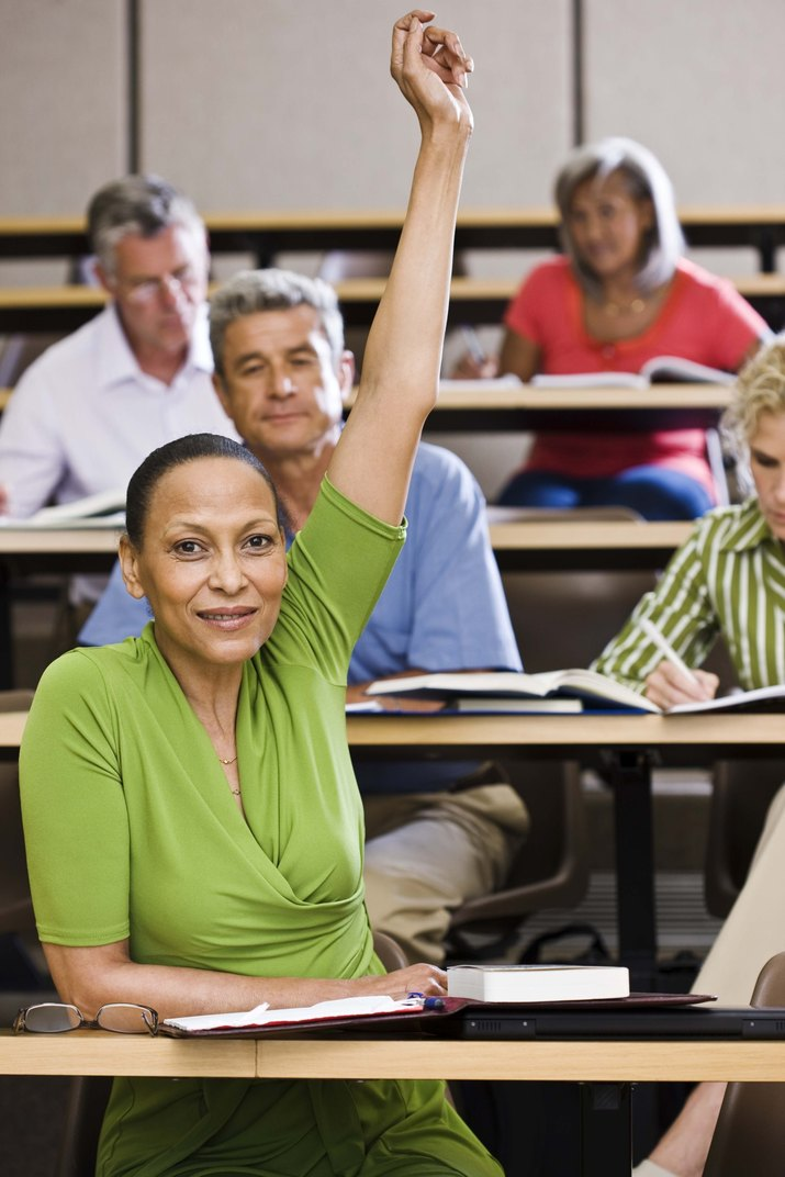 Student raising hand in lecture hall