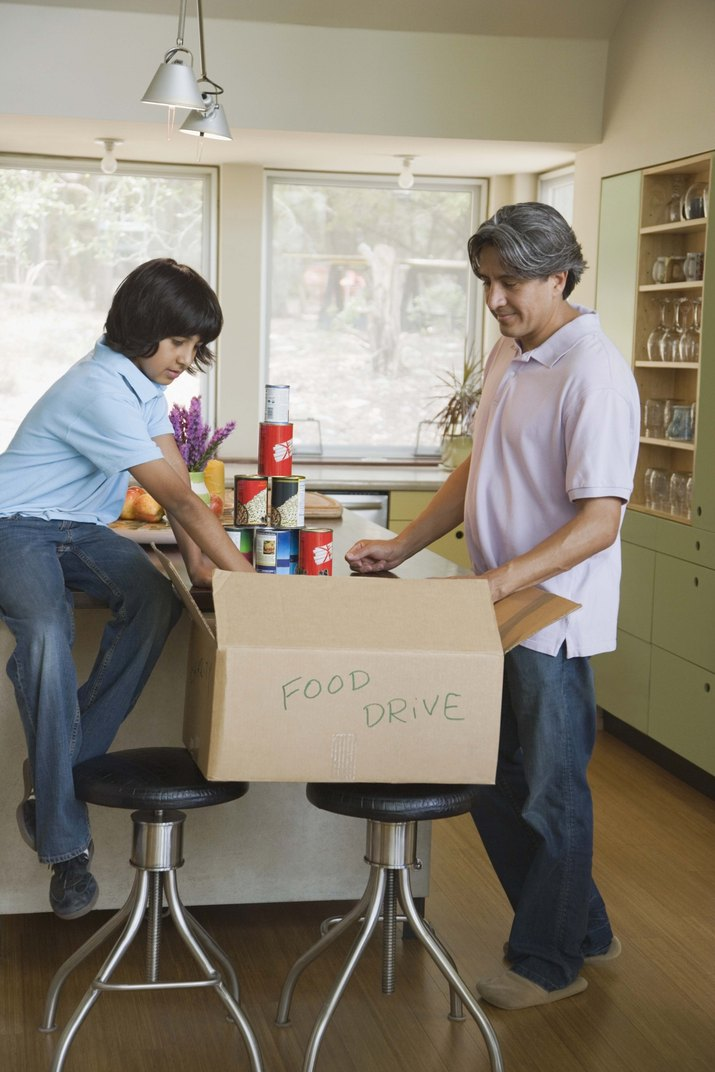 Father and son packing box of canned food