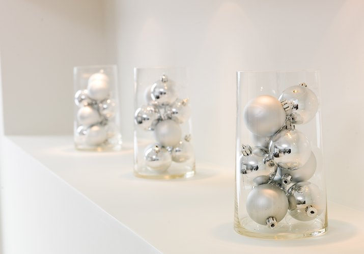 Glass containers of silver ornaments on mantle