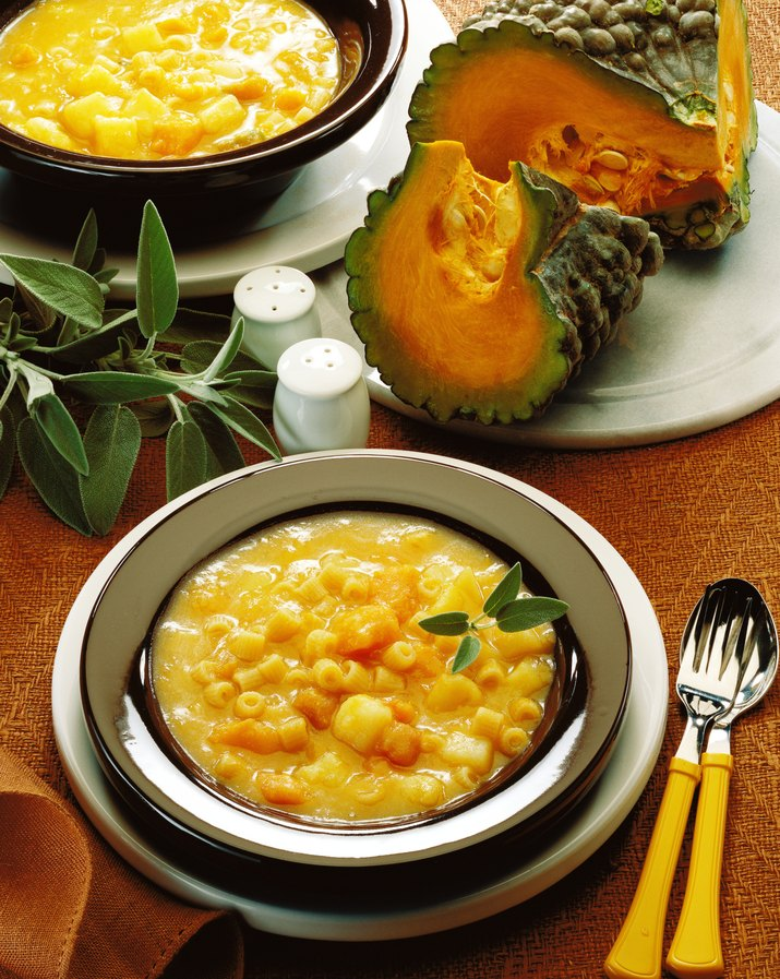 close-up of a bowl of pumpkin and macaroni kept beside pumpkin slivers and herbs