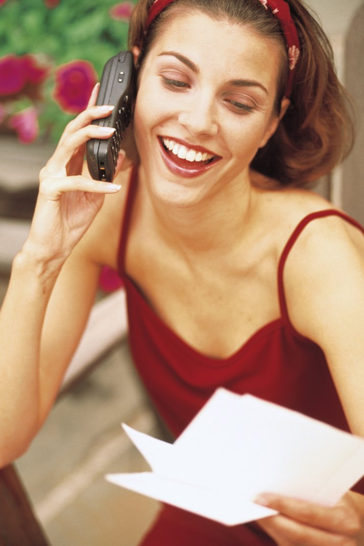 Woman talking on cell phone and holding letter or note